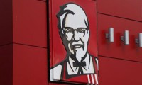 In this Tuesday, Oct. 9, 2012 photo, a close-up of a sign with a picture of Colonel Sanders is shown on the wall of a combination Kentucky Fried Chicken, Taco Bell in Doral, Fla. Fast-food operator Yum Brands Inc. said Tuesday its third-quarter net income rose by 23 percent, serving up a winning combo of across-the-board sales gains in the U.S. and a quick turnaround in its China market. The owner of the Taco Bell, Pizza Hut and KFC chains also raised its earnings guidance for the year. (AP Photo/Wilfredo Lee)